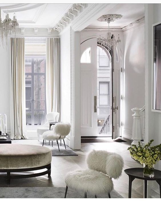 fur chairs and a velvet ottoman add chic to the space and look cozy