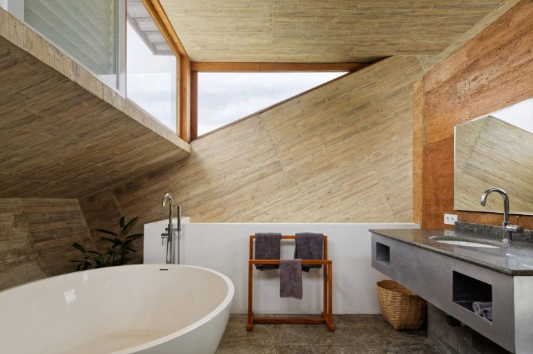 The en-suite bathroom features some windows, too, and there's a free-standing bathtub, a concrete vanity and much wood in the decor