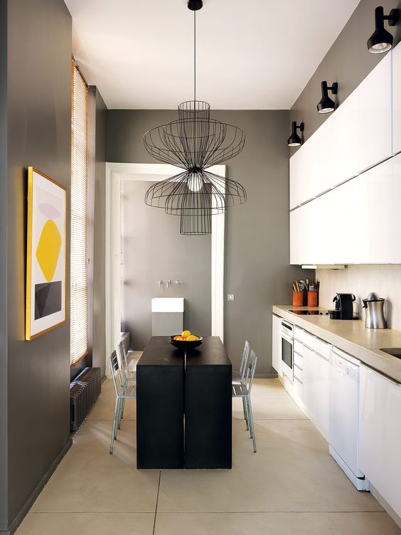 The kitchen is done in black, graphite grey and white, there's a matte back table and kitchen island in one and white cabinets, and of course a bold artwork to enliven it all