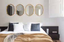 06 The master bedroom has vintage tile floors, a large upholstered bed and vintage framed mirrors instead of a usual headboard