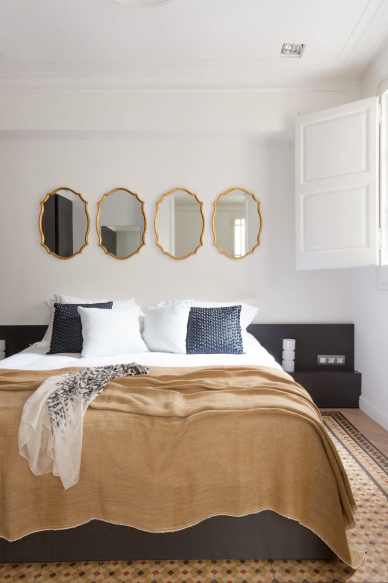 The master bedroom has vintage tile floors, a large upholstered bed and vintage framed mirrors instead of a usual headboard