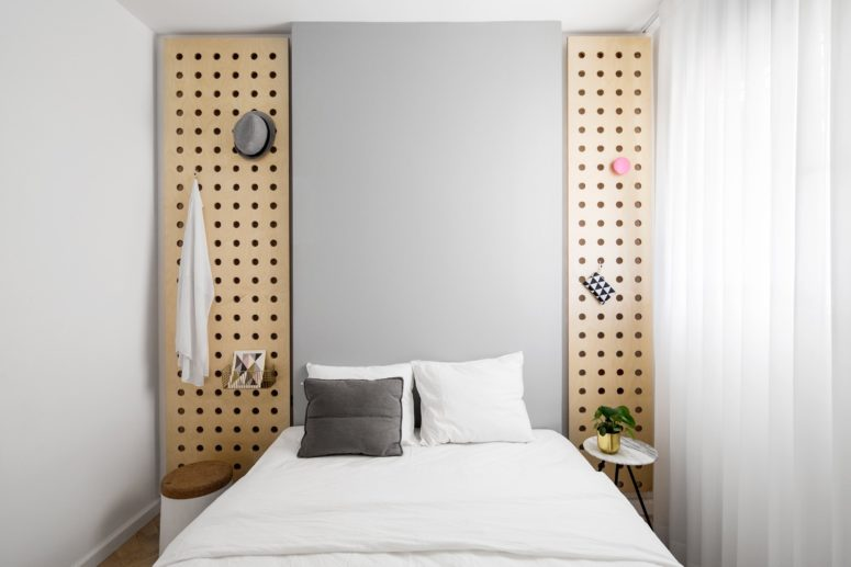 The master bedroom is small and simple, with cool wooden panels for storage and mismatching nightstands