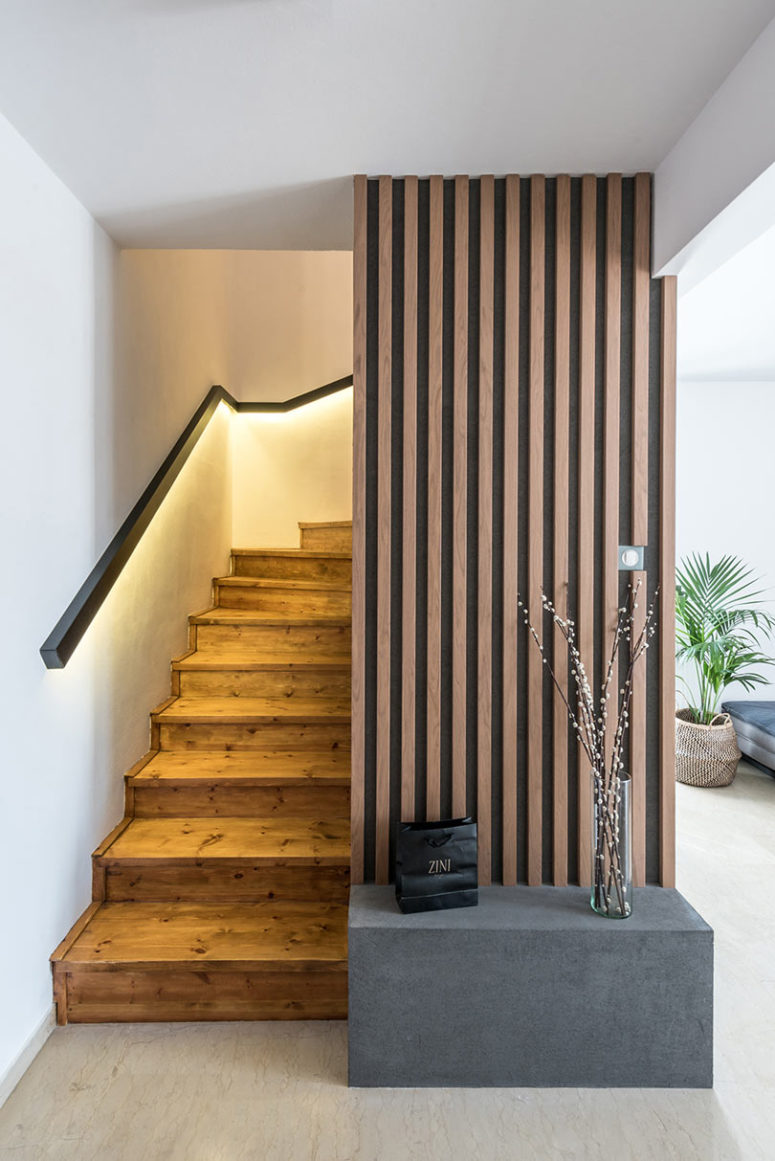 The staircase is wooden, with lit up railing and a concrete bench