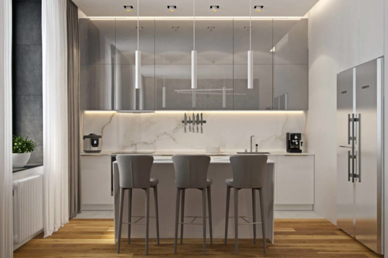 White marble, white cabinets and light grey lit up cabinets and chairs look soothing and heavenly