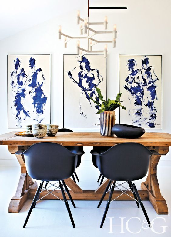 a gorgeous modern dining space with a trestle wooden table and black chairs