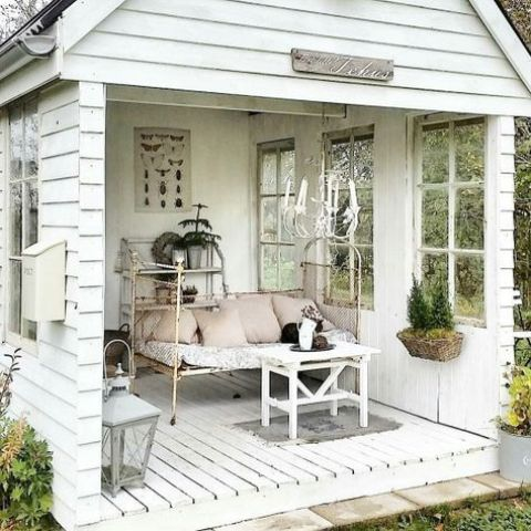 a shabby chic she shed in white, with a retro daybed, lanterns and some potted plants