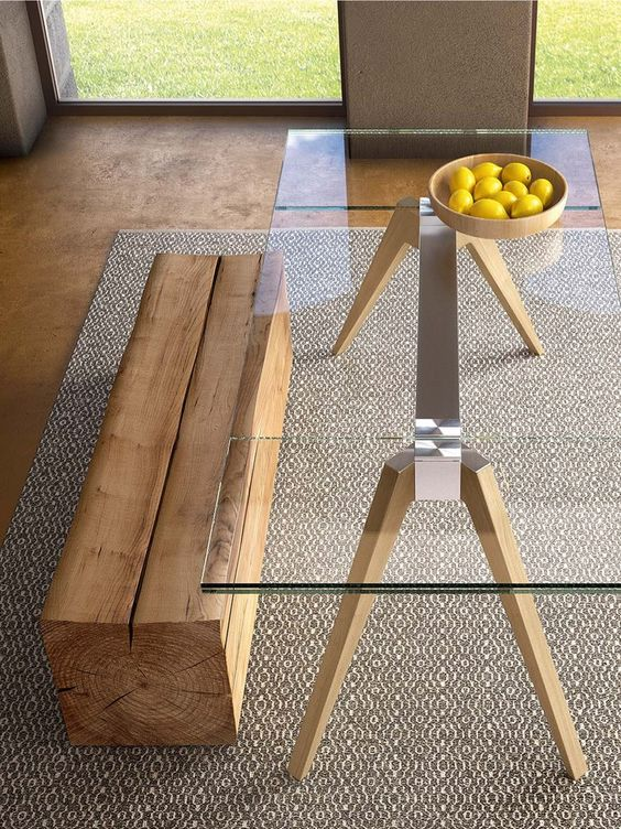a table with a metal frame and wooden legs, a clear glass tabletop and a piece of wood as a bench for both a modern and rustic look