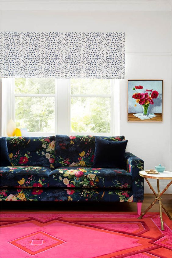 the colorful room in pink and red is made calmer with a navy floral print sofa