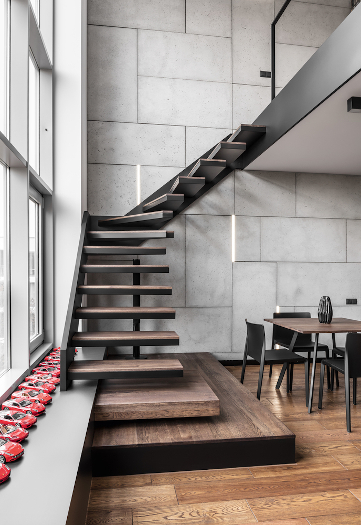 Blackened metal is softened with natural wood, and a floating design gives an industrial touch to the space