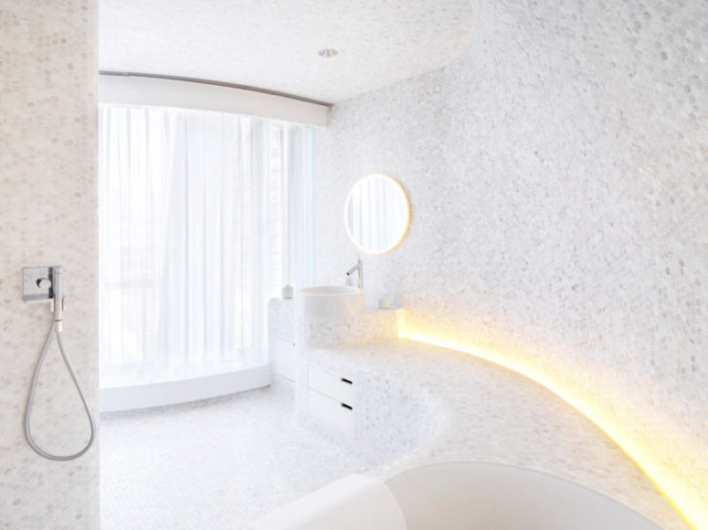 The first bathroom is clad with penny hex tiles in marble shades, there's much natural and artificial light