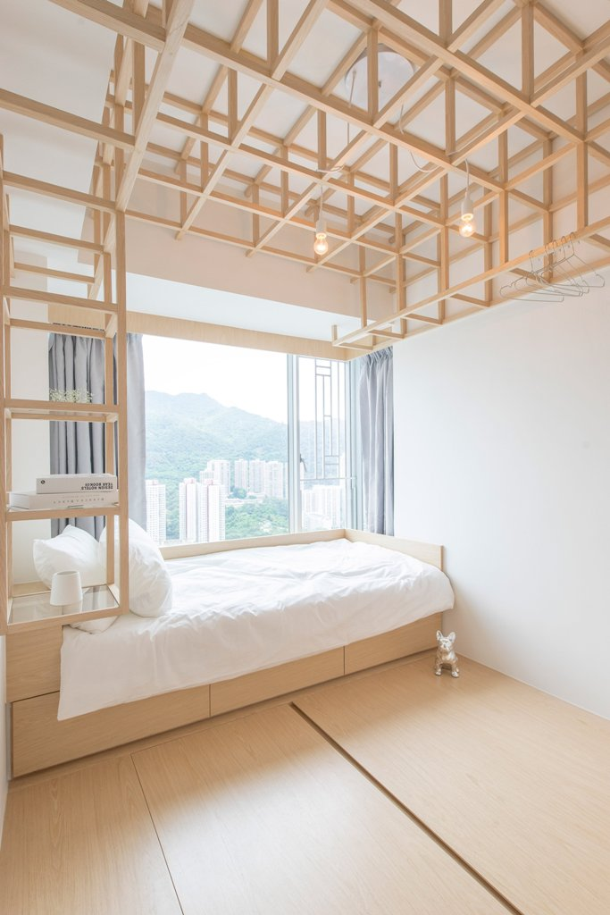 The guest bedrom features a bed and wooden frames over it that come into shelves in the headboard, looks super creative