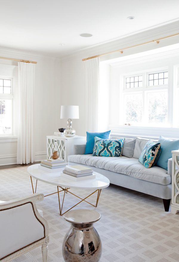 The living room is neutral, with blue pillows and eclectic furniture