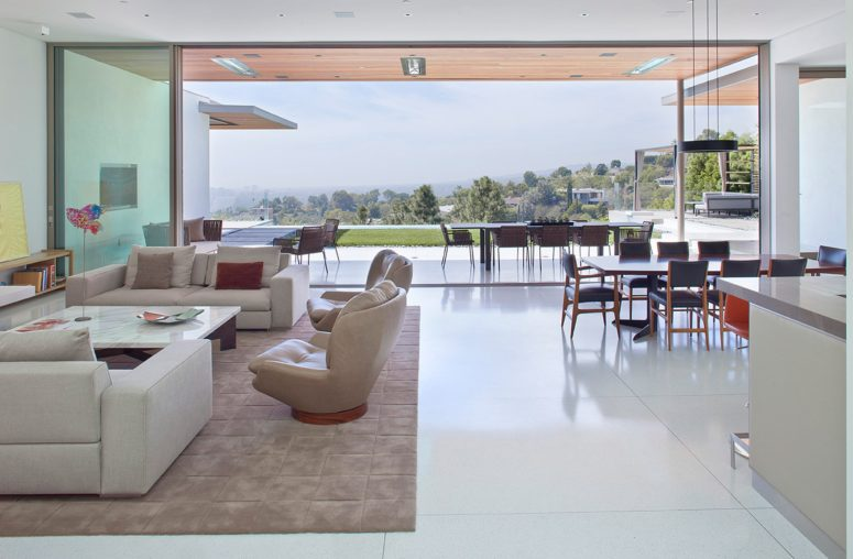 The living room, kitchen and dining room are united into one open space layout, and there's a separate outdoor dining zone