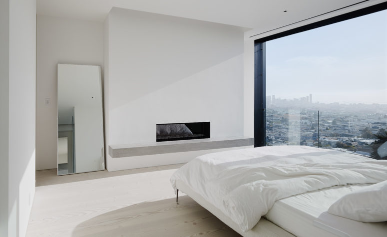 The master bedroom features a glazed wall with jaw-dropping views, a built-in fireplace and a large bed