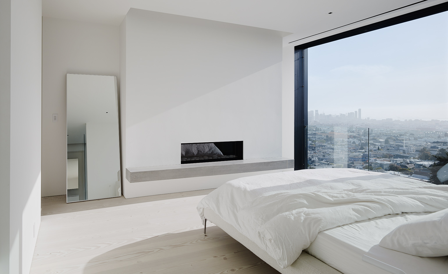 The master bedroom features a glazed wall with jaw dropping views, a built in fireplace and a large bed