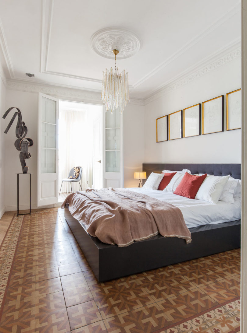 The second bedroom features a large bed, a glam chandelier and a sculpture in the corner