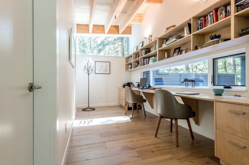 The shared working space features bookshelves over the desk and some windows instead of a usual wall to open up the space and fill it with light