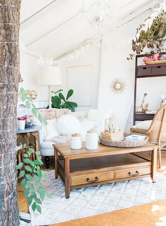 a boho living room in white with natural wood touches, a refined chandelier and potted plants