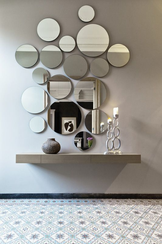 a circle wall mirror arrangement looks cool and modern, such an unusual decor idea