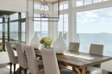 a coastal dining space with a view looks cozier with a rustic dining table