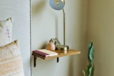 07 a small wooden nightstand attached to the wall can hold several necessary objects