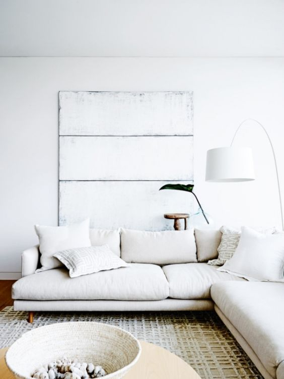 a whitewashed wooden board and a rope basket add texture to the living room