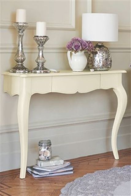 an antique desk was cut and repainted to use it as a small console table for a tight vintage space