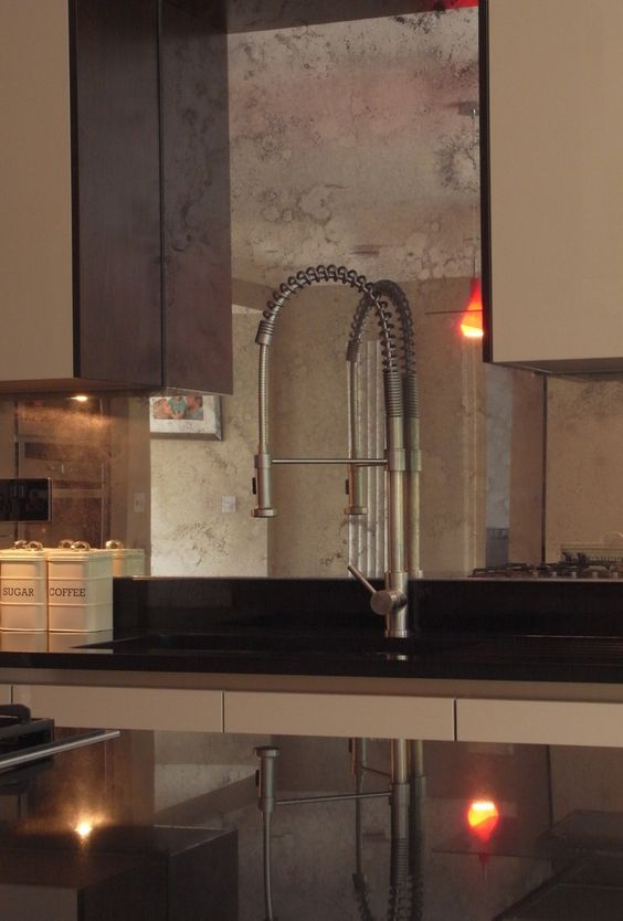 copper faded mirror backsplash is a perfect fit for a warm-colored brown kitchen, it adds chic