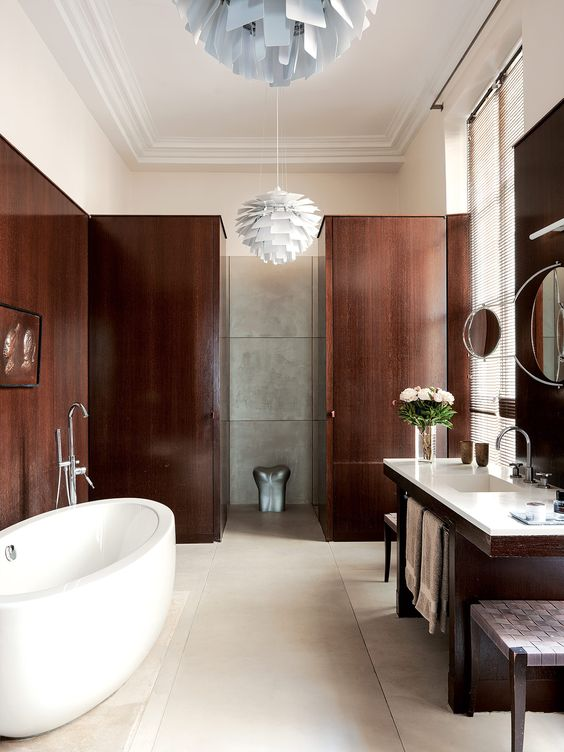 The bathroom is decorated with a refined feel yet looks very cozy due to the choice of dark stained wood for panels and furniture
