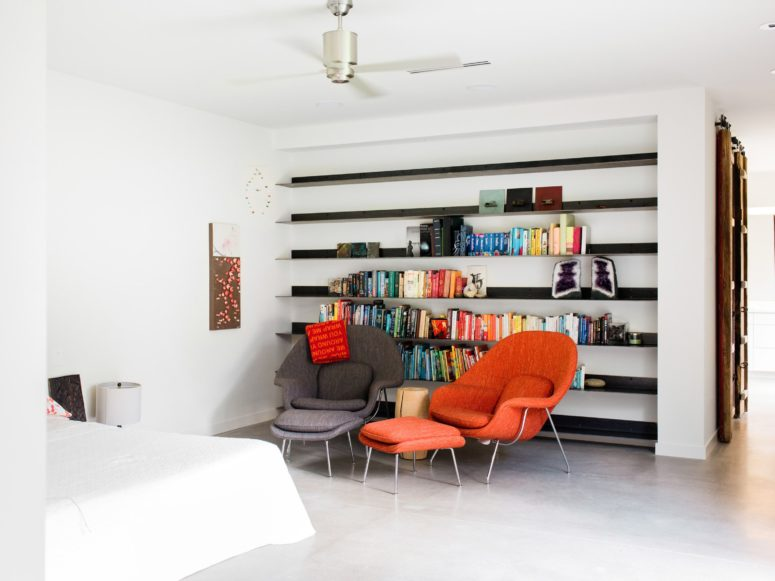 The bedroom features a large bed and a sitting zone with colorful chairs and one wall is taken by open shelves