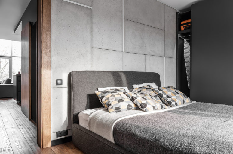 The bedroom is simple and functional, and concrete panels are made cozier with an upholstered bed