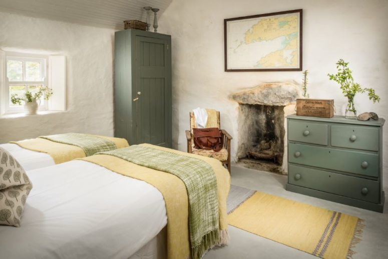 The guest bedroom is decorated in muted green and yellow, there's an antique hearth and a small window