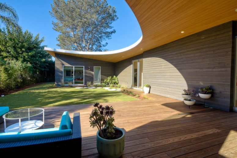 The house wall and the deck are clad with the same wood, which makes the space more inviting and cool