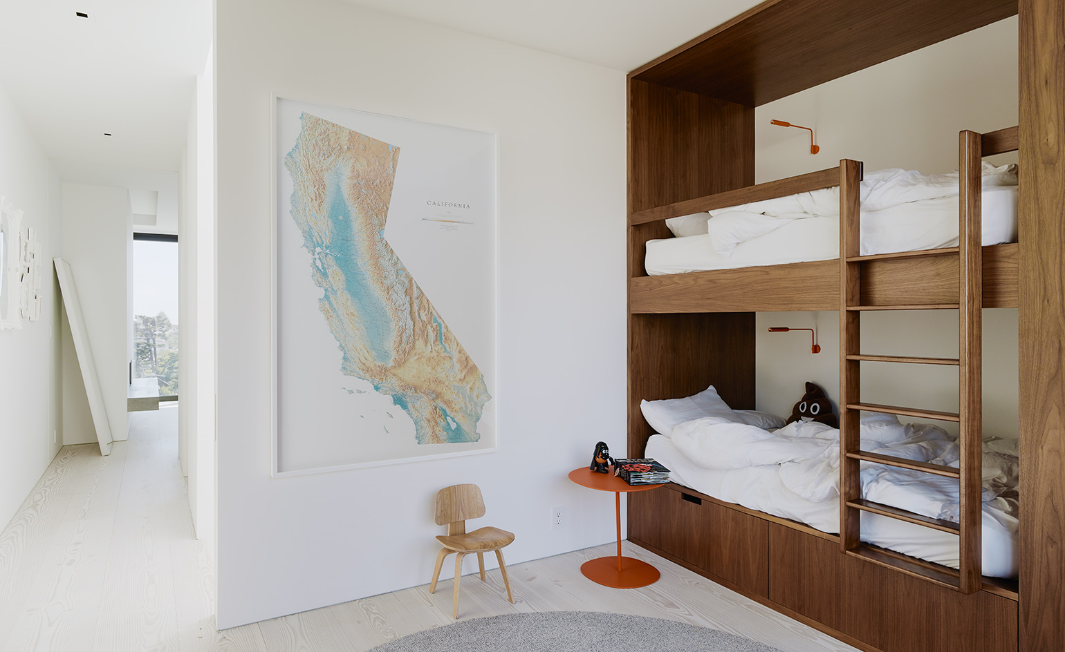 The kids' bedroom has a wooden bunk bed, a map on the wall and some small accessories