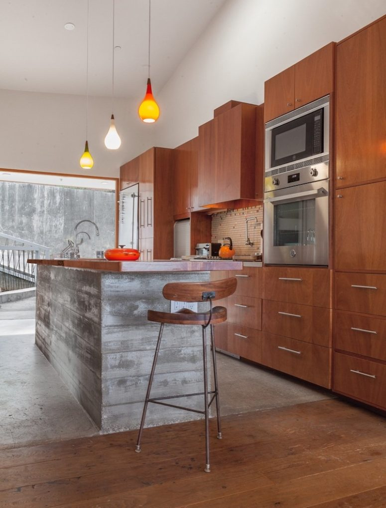 The kitchen is clad with warm-colored wood and there's a large kitchen island of concrete and wood