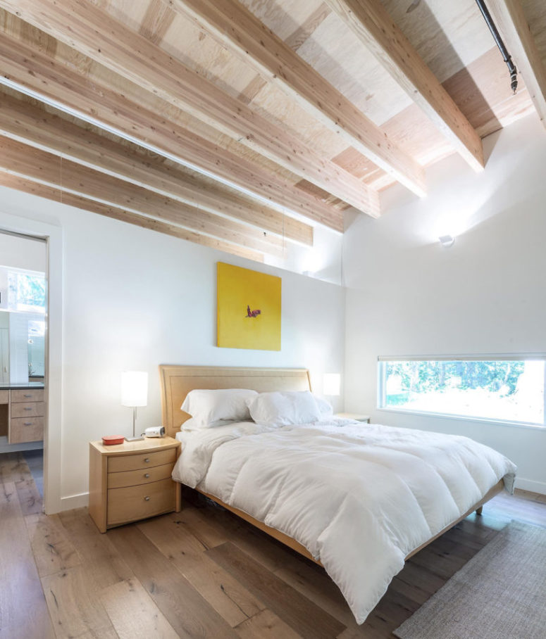 The master bedroom features wooden beams, floors, furniture and a narrow horizontal window to keep privacy, which makes it very cozy