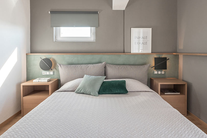The master bedroom is done in grey and mint, with additions of natural wood