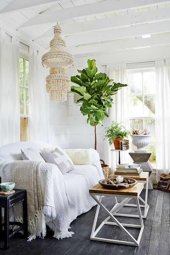 a boho living room she shed with a unique chandelier and potted plants looks super inviting