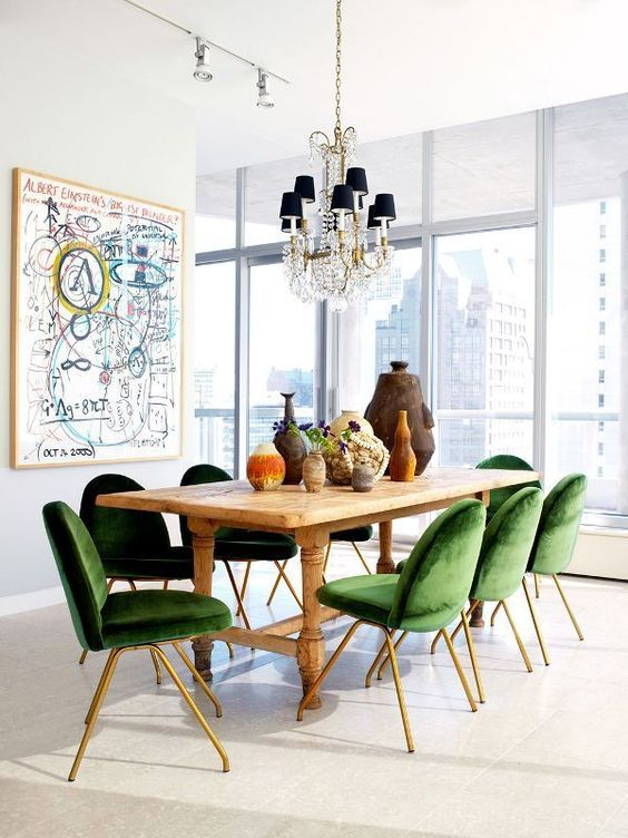a dining space is enlivened and spruced up with emerald velvet dining chairs with brass legs