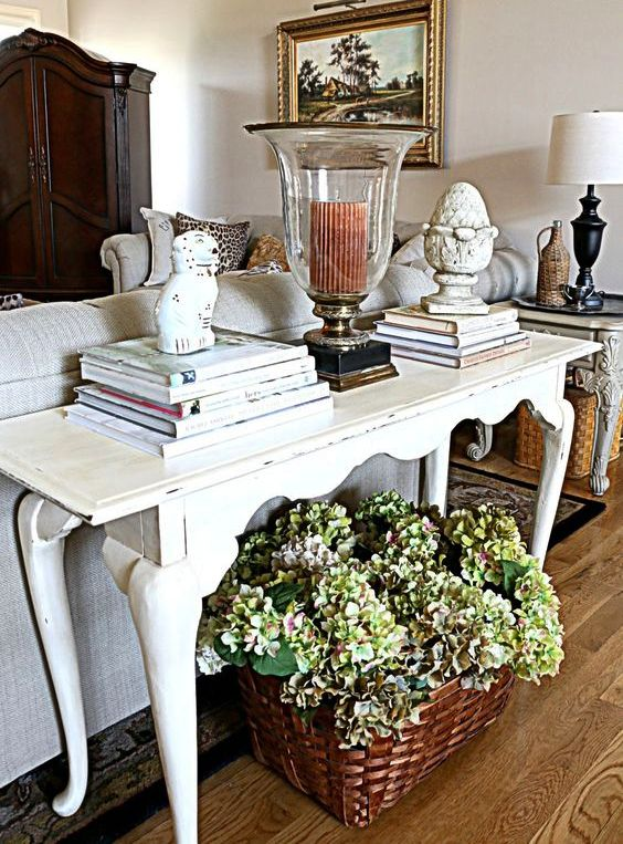 a traditional living room with a white vintage desk used as a console table