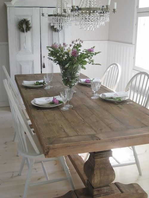 a whitewashed shabby chic dining room is enlivened with a large wooden trestle dining table