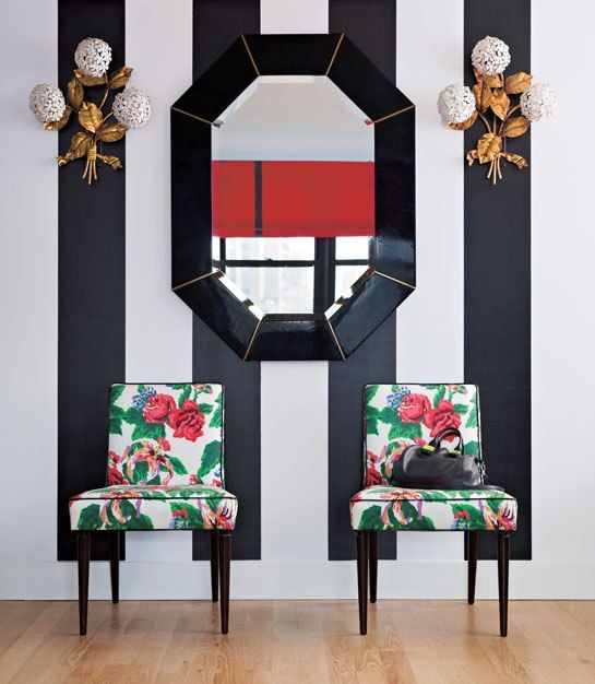 an art deco entryway in black and white is spruced up with bold green and red floral print chairs