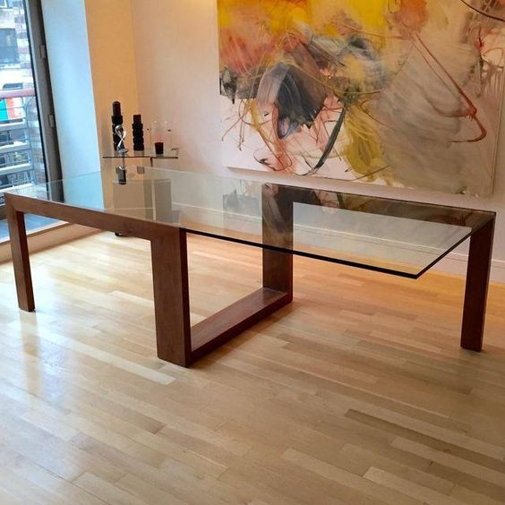 modern sculptural table with a creative geo wooden frame and a large glass table top
