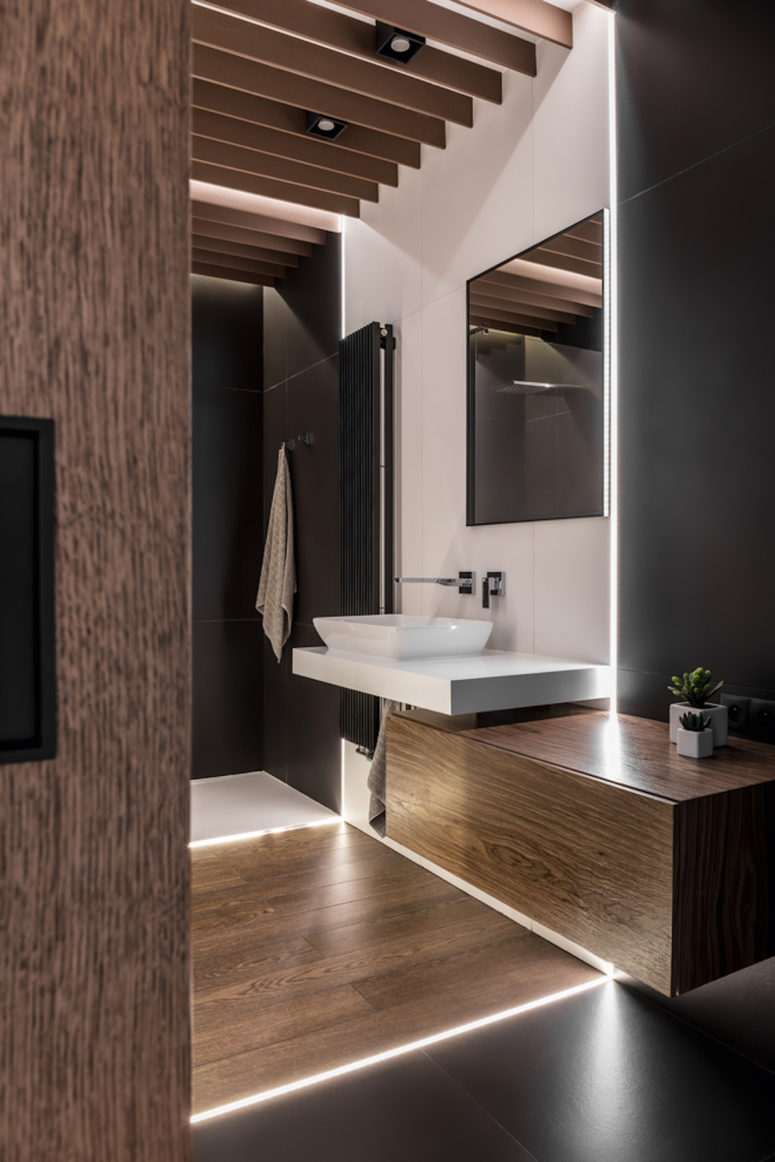 The bathroom is done in the same colors and with wood for coziness, additional lights make it feel welcoming though the colors are rather dark