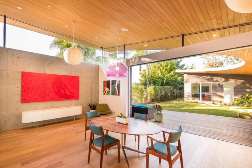 The dining space features mid century modern furniture and bright artworks plus skylights