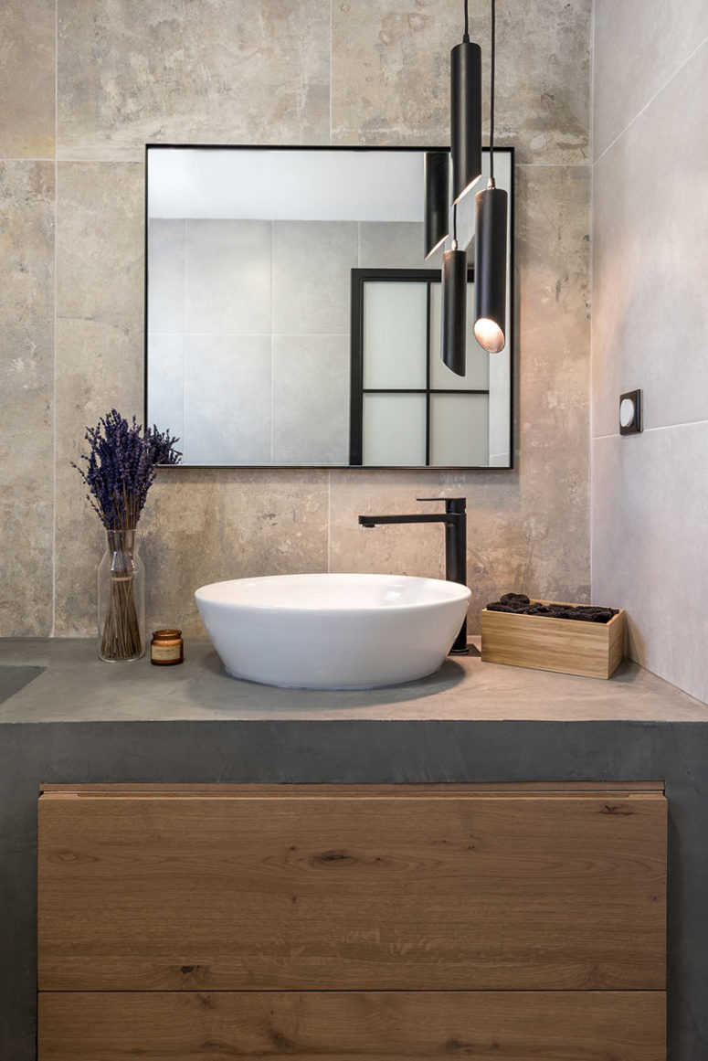 The master bathroom is clad with stone tiles, and the vanity is concrete, modern pendant lamps add a contemporary feel