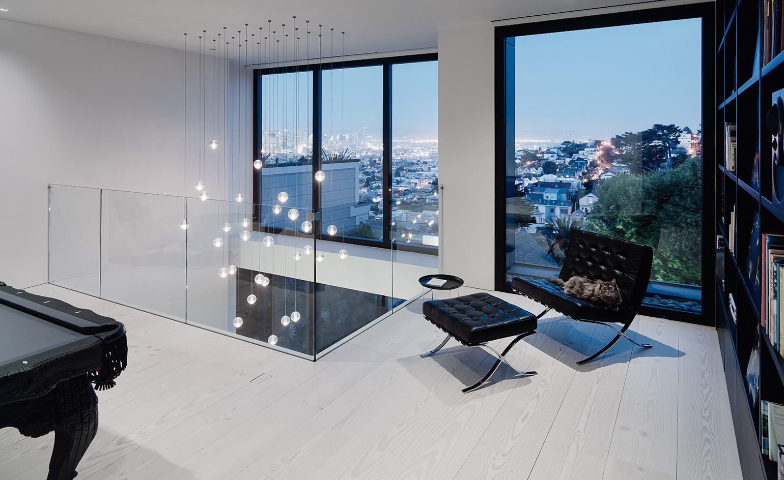 The top floor features a social area with a pool table and bookcases, the furniture is black and it contrasts white surroundings