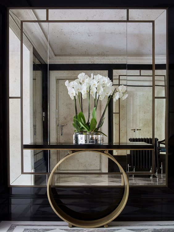 a gorgeous framed mirror in a black backdrop is complemented with a narrow console on a circle base