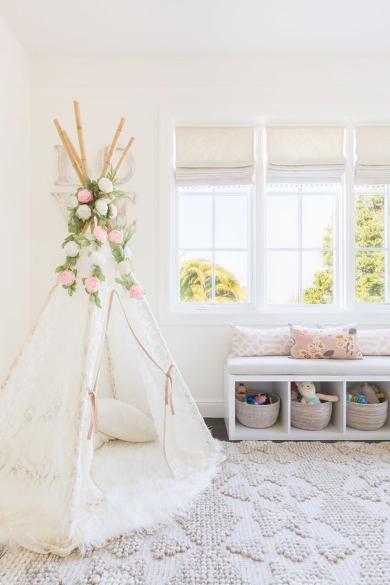 a play nook with a white lace teepee, a window bench with toy storage for a girl's playroom
