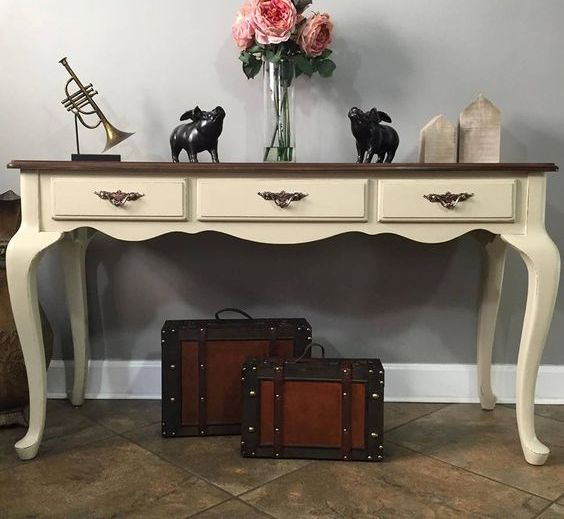 a vintage desk painted light yellow as an entryway console for vintage feel